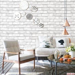 Fifties Sessel und graues Sofa um Couchtisch unter Pendelleuchten mit kupferfarbenem Schirm in loftartigem Ambiente mit Wandtell